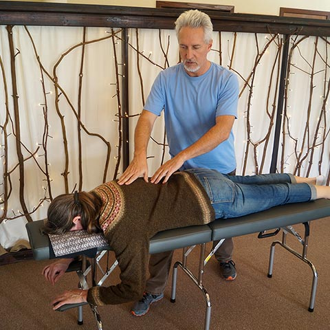 Chiropractor Luke Schmelzle with patient using Network Spinal Analysis (NSA) technique